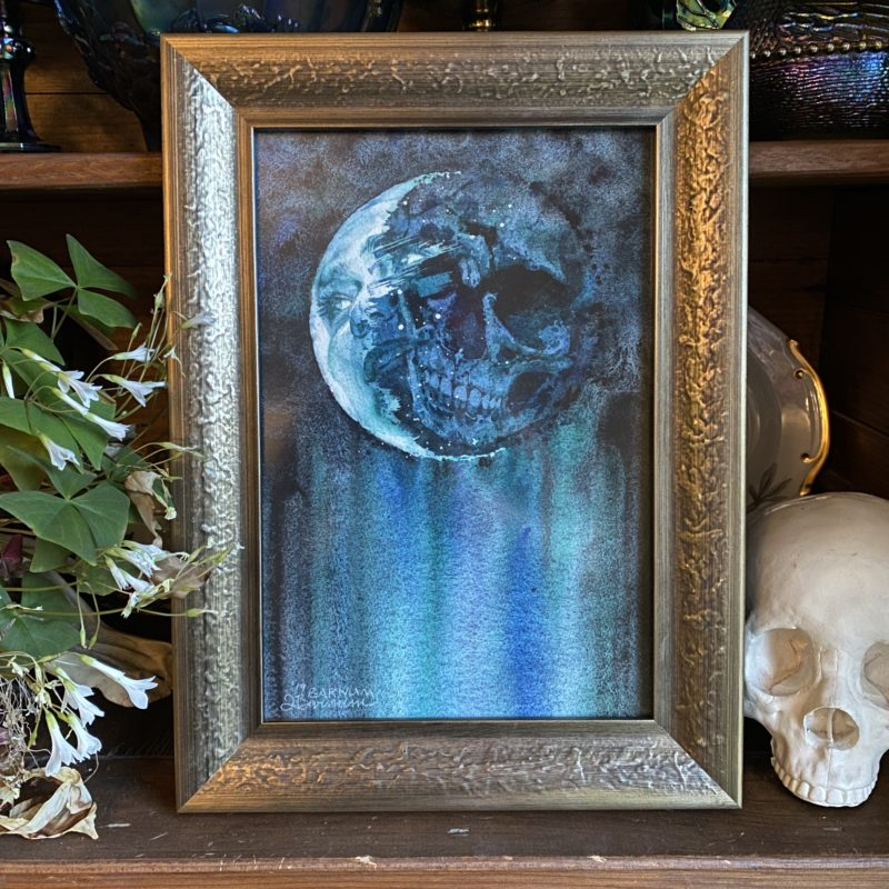 """Lunar Lurker,"" watercolor on paper of a face and skull in the moon. Presented in a silver frame."