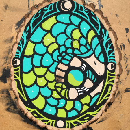 A vibrant pangolin painted with a bright turquoise and lime green sits curled up in the center of a decorative border consisting of vines, leaves, and phases of the moon on a black background.