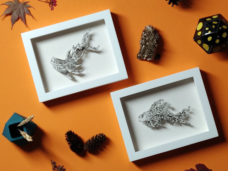 Daria Aksenova. Hand-cut illustration of a space cloud shaped like a fish suspended in a shadowbox structure.