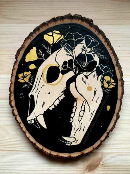 A painting on a wood slice featuring a bear skull against a black background with golden poppies entangled around the skull.